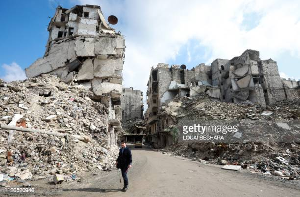 People walk past the rubble of buildings that were heavily damaged or destroyed during battles between rebel fighters and regime forces, in the...