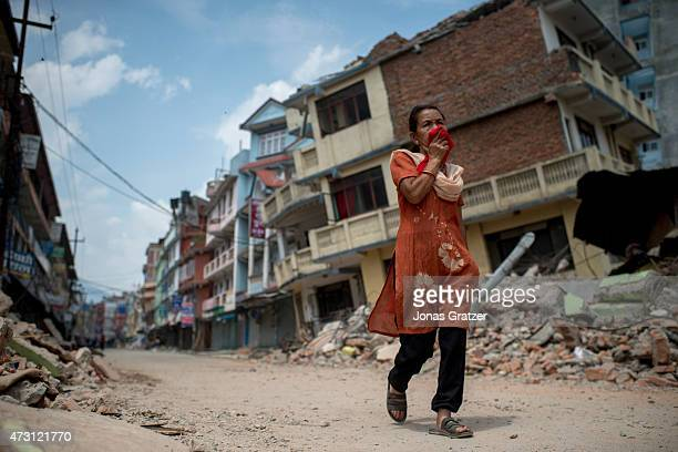 People walk past the rubble of destroyed buildings following a second major earthquake May 13 2015 in Kathmandu Nepal A 73 magnitude earthquake...