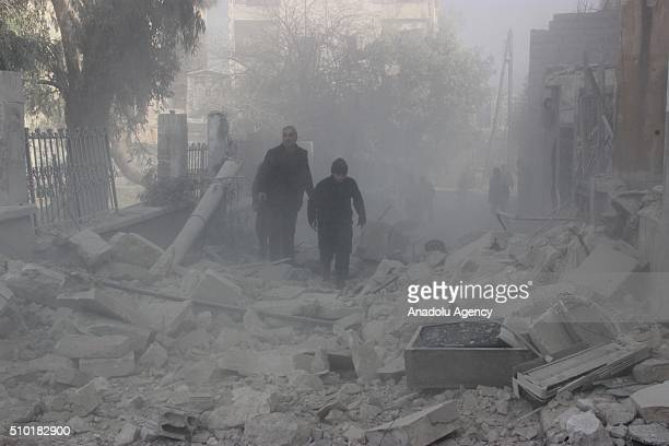 People walk past the rubbles of damaged buildings after the Russian airstrikes targeted residential areas in opposition controlled El Zebdiye...