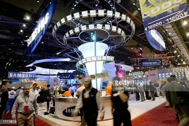 People walk past the Samsung booth at the 2003 International Consumer Electronics Show January 9 2003 in Las Vegas The show is expected to draw over...