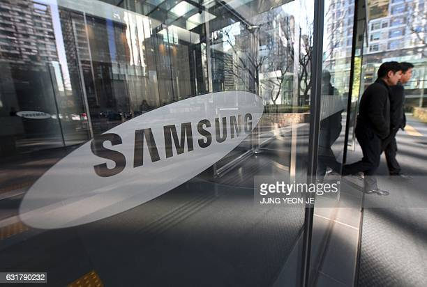 People walk past the Samsung logo at the Samsung group headquarters in Seoul on January 16 2017 South Korean prosecutors on January 16 sought the...