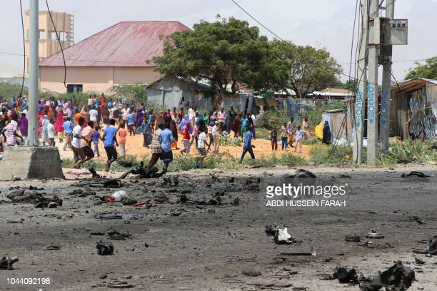 People walk past the scene of a suicide bomb attack in the capital Mogadishu on October 1 2018 after a suicide bomber rammed a vehicle loaded with...