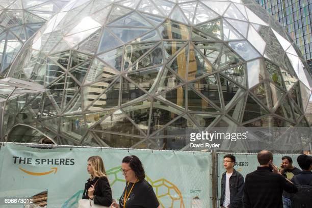 People walk past the signature glass spheres under construction at the Amazon corporate headquarters on June 16 2017 in Seattle Washington Amazon...