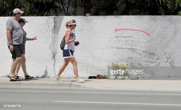 People walk past the site of a crash on May 12 where a Tesla Model S sedan crashed into a concrete wall in Ft Lauderdale Fla The driver of the Tesla...