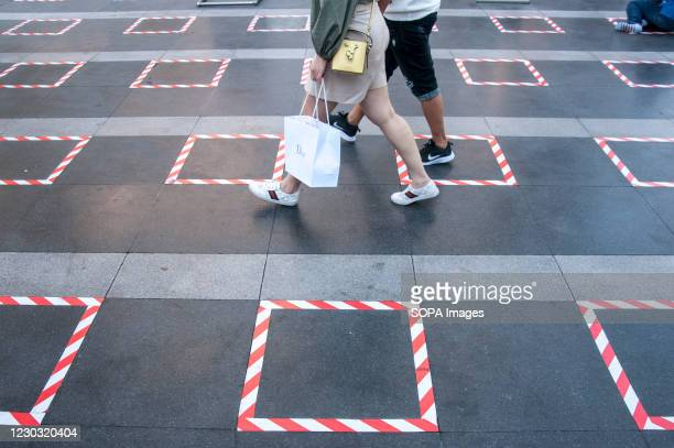 People walk past the social distancing squares in front of the shrine. The Thai government has applied social distancing measures for department...