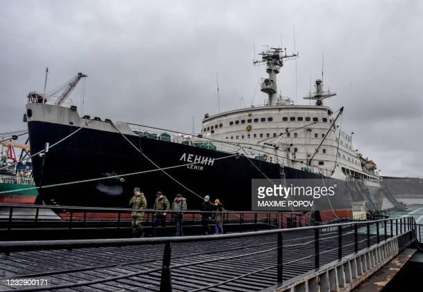 People walk past the Soviet nuclear-powered icebreaker 'Lenin' moored in the port of Murmansk, northwest Russia, on May 14, 2021. - Icebreaker...