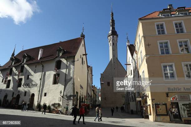 People walk past the spire of Tallinn Town Hall in the historic city center on March 24 2017 in Tallinn Estonia Tallinn's old town escaped...