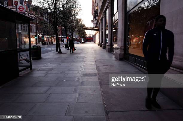 People walk past the temporarily closed department store Selfridges on a near-deserted Oxford Street in London, England, on March 26, 2020. According...