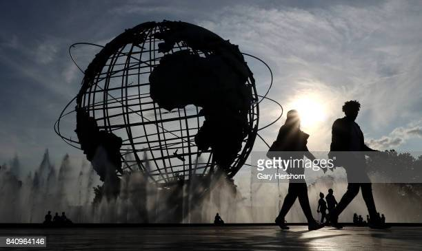 People walk past the Unisphere, a spherical stainless steel representation of the Earth built for the 1964 World's Fair in Flushing Meadows Corona...