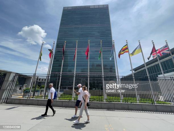 People walk past the United Nations headquarters building on the East Side of Manhattan,in New York City, on June 8, 2021.