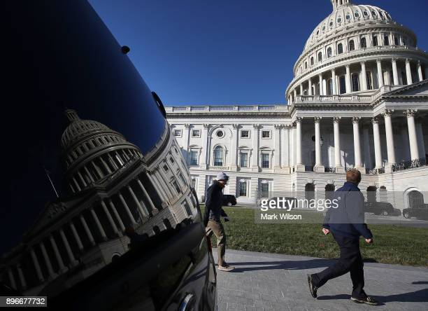 People walk past the US Capitol as congressional lawmakers work on a deal to fund the government and avert a shutdown by midnight Friday on December...