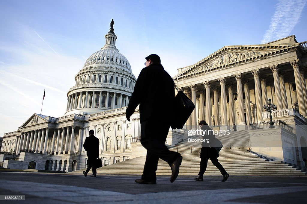People walk past the U.S. Capitol in Washington, D.C., U.S., on Thursday, Jan. 3, 2013. The 113th Congress convenes today in Washington where new members will try to meld their diverse backgrounds in a legislature containing a record seven openly gay lawmakers, an unprecedented 20 women in the Senate and the first all-female state delegation, from New Hampshire. Photographer: Pete Marovich/Bloomberg via Getty Images