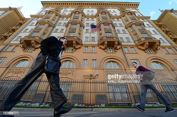 People walk past the US Embassy in Moscow the headquarters of US Agency for International Development Russia's mission on September 20 2012 Russia...