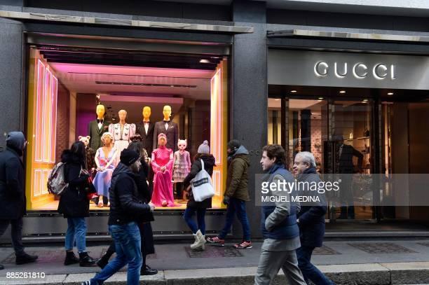 People walk past the window of Italian fashion shop Gucci on December 4 in via Montenapoleone a highclass shopping district in Milan Italian fashion...