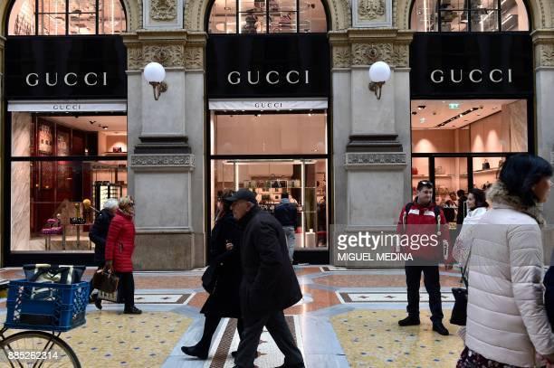 People walk past the window of Italian fashion shop Gucci on December 4 in the Vittorio Emanuele II gallery in Milan Italian fashion giant Gucci said...