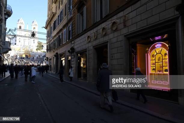 People walk past the window of Italian fashion shop Gucci on December 4 in via Condotti a highclass shopping district near Piazza di Spagna in Rome...