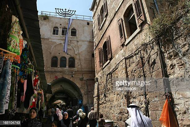 People walk past the Wittenberg House in the Muslim Quarter of Jerusalem's Old City on July 14 2008 The house previously owned by former Israeli...