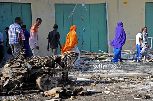 People walk past the wreckage of a car at the site of a bomb blast near Makka alMukarama Road in Mogadishu on December 19 2015 Several people were...