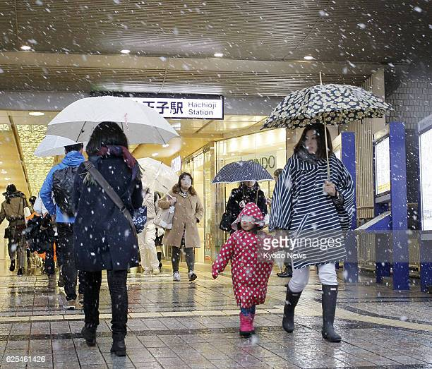 People walk past Tokyo's JR Hachioji Station on their way to their offices and schools on the morning of Nov 24 the day when the Japanese capital had...