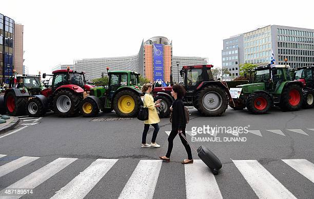 People walk past tractors parked in front of the European Commission during a farmers demonstration protesting against plunging food prices and...