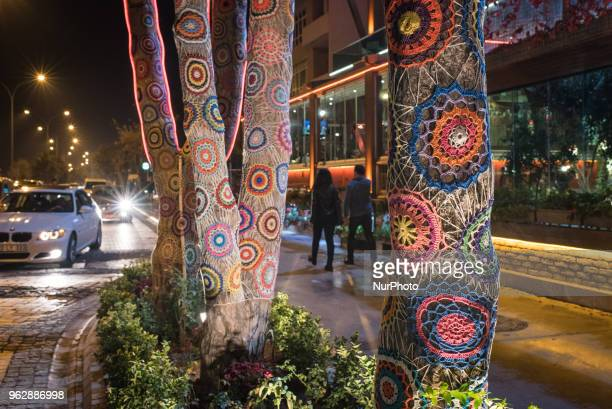 People walk past trees with knitted yarn art patterns in the streets of the Black Sea city of Samsun Turkey on 18 November 2017