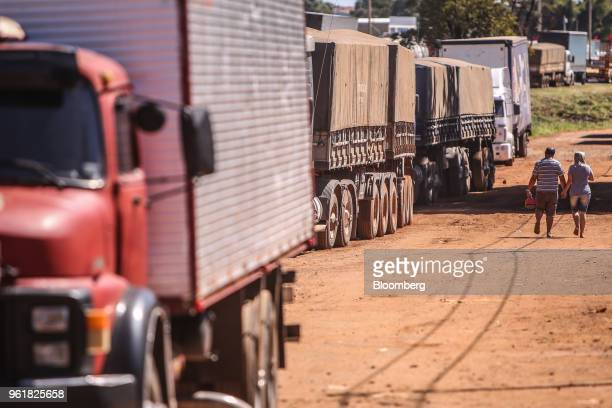 People walk past trucks parked on BR 040 highway during a protest against rising fuel prices in Luziania Brazil on Wednesday May 23 2018 Brazilian...