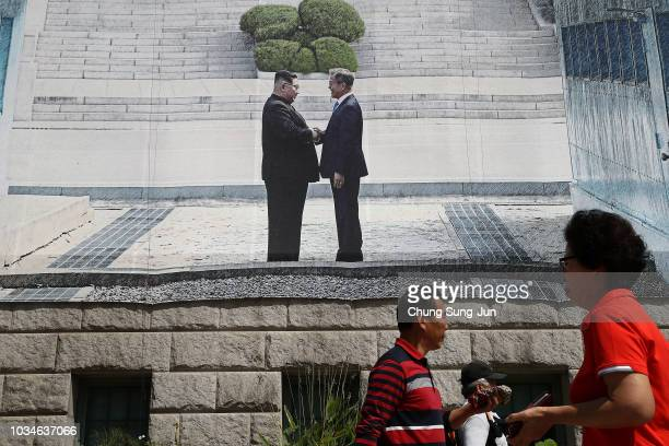 People walk past under a banner showing South Korea President Moon Jaein and North Korean leader Kim Jong Un to support the upcoming interKorean...