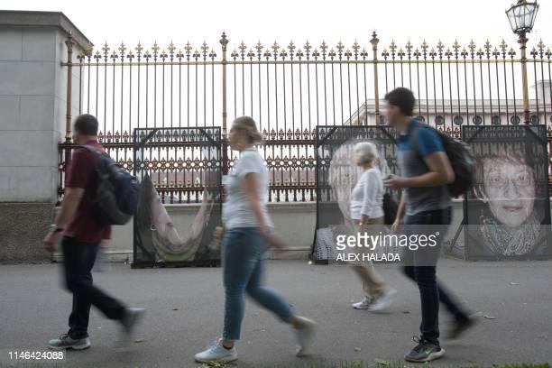 People walk past vandalised largeformat pictures of Holocaust survivors taken by GermanItalian photographer Luigi Toscano during his outdoor...