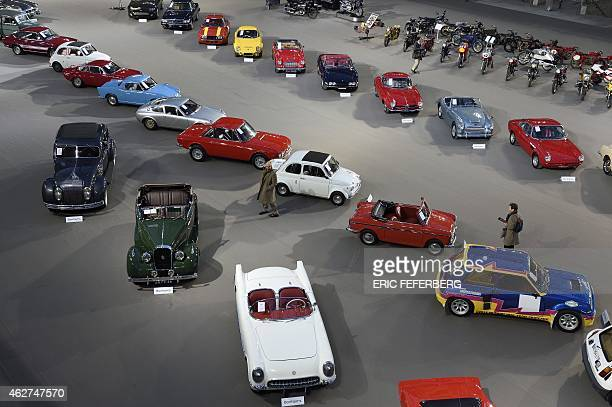 People walk past vehicles displayed at the Bonhams car and moto auction on Fabruary 4 2015 in Grand Palais in Paris Bonhams is the largest auction...