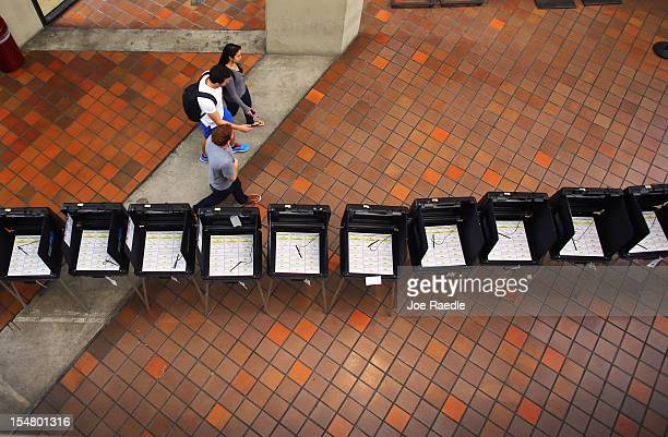 People walk past voting booths ready for early voting at the Stephen P Clark Government Center on October 26 2012 in Miami Florida Early voting in...