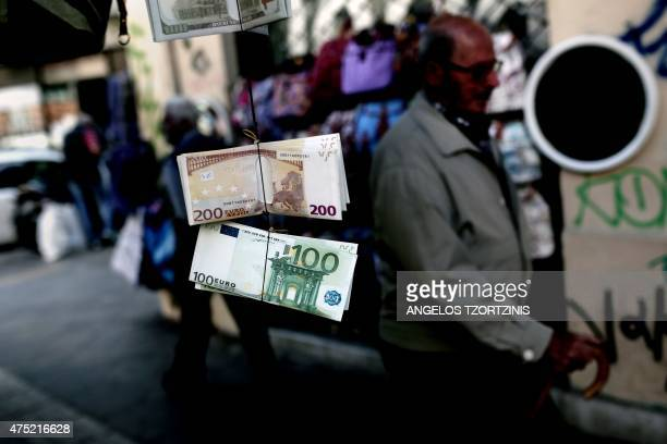 People walk past wallets whose exteriors are made in the image of Euro banknotes hanging outside a kiosk in Athens on May 30 2015 The Greek...