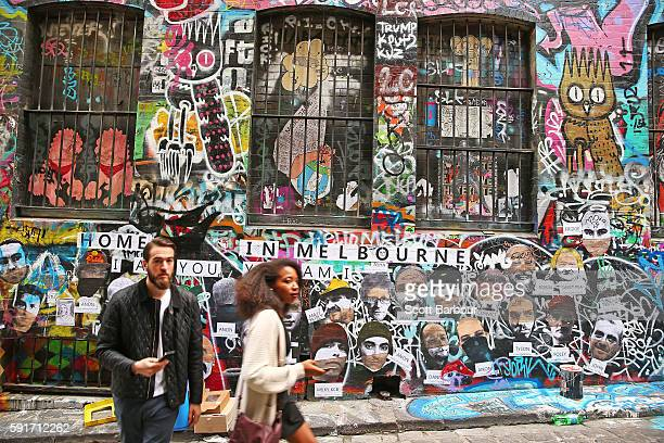 People walk past walls adorned with graffiti in Hosier Lane one of Melbourne's iconic laneways on August 18 2016 in Melbourne Australia Melbourne has...