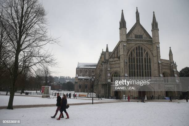People walk past Winchester cathedral in the snow in Winchester in south west England on March 2 2018 The Met Office has issued 10 severe weather...