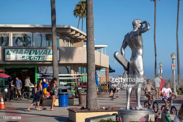 People walk, ride and skateboard on the sidewalk past businesses and the the Ben Carlson memorial statue near the pier on a summer day Monday, July...