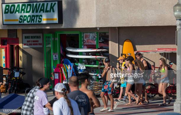 People walk, ride and skateboard on the sidewalk past businesses near the pier on a summer day Monday, July 20, 2020 in Newport Beach, CA.
