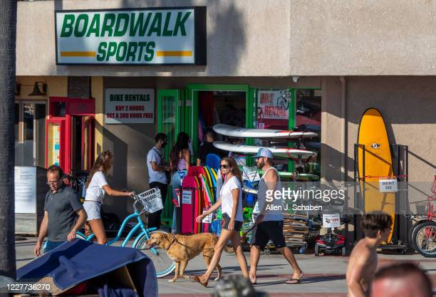 People walk, ride and skateboard on the sidewalk past businesses on a summer day Monday, July 20, 2020 in Newport Beach, CA.