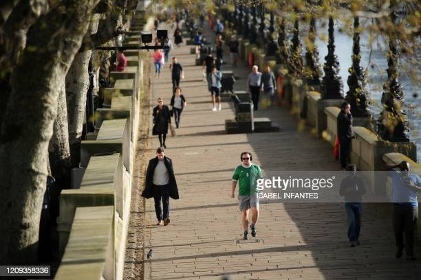 People walk run and jog along the South Bank by the River Thames to take their daily exercise allowance in central London on April 7 as life in...