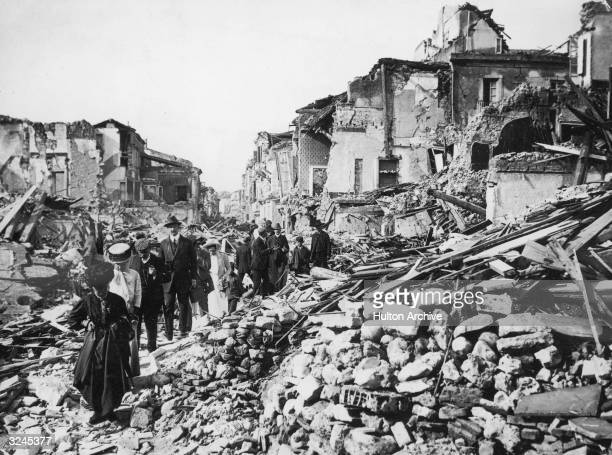 People walk singlefile through the rubble of ruined buildings after a large earthquake in Messina Italy