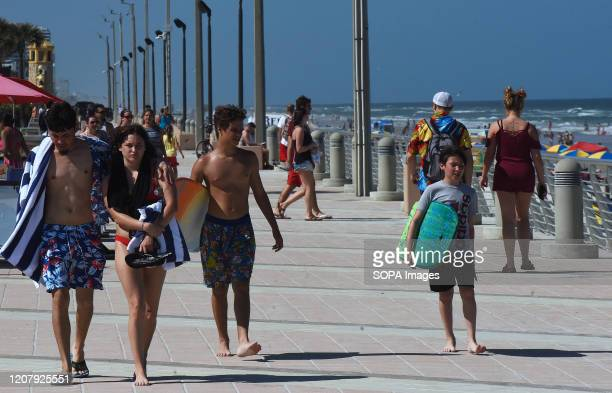 People walk the boardwalk during a spring break at Daytona Beach after Florida Governor Ron DeSantis refused to order the state's beaches closed as...