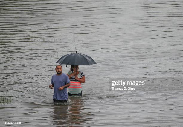 People walk the flooded waters Hopper Rd on September 19 2019 in Houston Texas Gov Greg Abbott has declared much of Southeast Texas disaster areas...