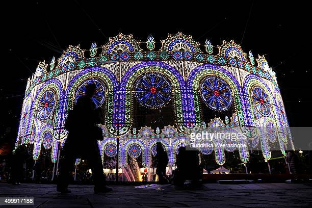 People walk the site an illuminated structure surrounding a fountain as a part of the 21th Kobe Luminarie on December 4 2015 in Kobe Japan This...