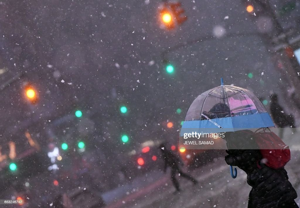 People walk the snow and sleet-covered streets of New York on March 14, 2017. Winter Storm Stella unleashed its fury on much of the northeastern United States on March 14 dropping snow and sleet across the region and leading to school closures and thousands of flight cancellations. Stella, the most powerful winter storm of the season, was forecast to dump up to two feet (60 centimeters) of snow in New York and whip the area with combined with winds of up to 60 miles per hour (95 kilometers per hour), causing treacherous whiteout conditions. But after daybreak the National Weather Service (NWS) revised down its predicted snow accumulation for the city of New York, saying that the storm had moved across the coast. PHOTO / Jewel SAMAD