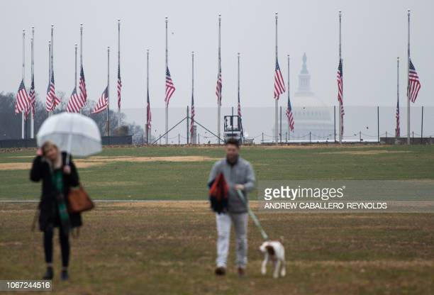People walk their dog near US flags flying at halfstaff at the Washington Monument in tribute to former US President George H W Bush on December 1 in...