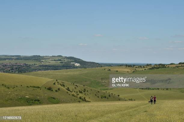 People walk their dog on Mount Caburn, a prominent high point on the South Downs east of Lewes in southern England on May 31, 2020 on the eve of a...