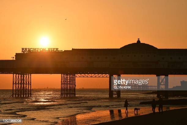 People walk their dog on the beach as the sun sets behind the Palace Pier in Brighton on the south coast of England on March 22 2020 Up to 15 million...