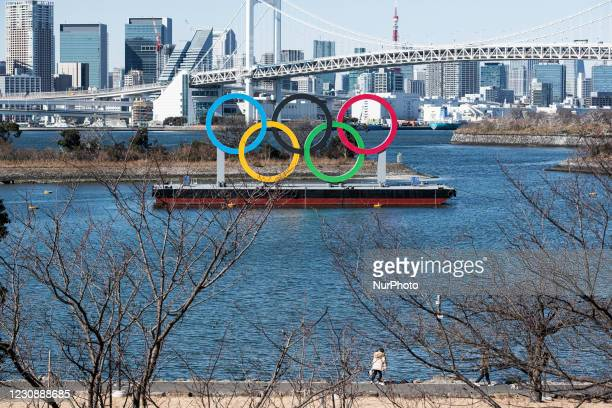 People walk their dogs along the coast where displayed the Olympic Symbol at the Odaiba marine park in Tokyo, Japan on 30 January, 2021.