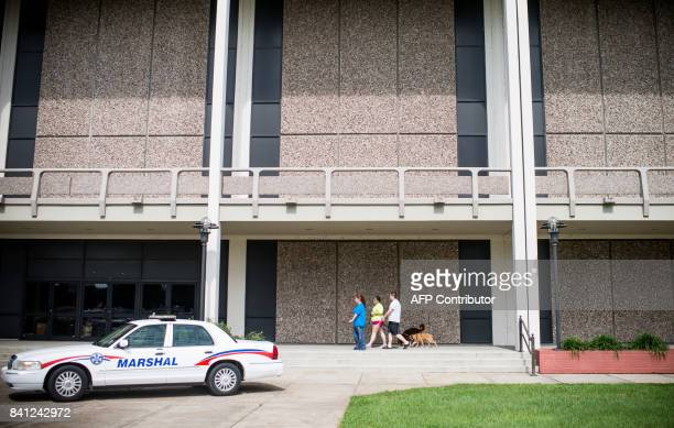 People walk their dogs at the Lake Charles Civic Center in Lake Charles Louisiana on August 29 2017 Louisiana authorities scrambled to safeguard...
