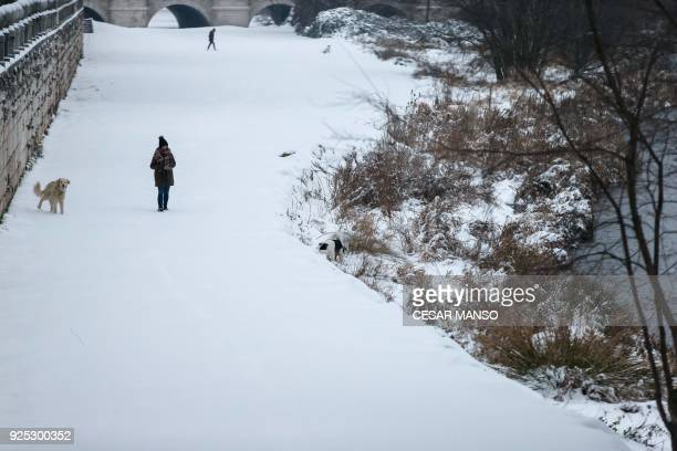 People walk their dogs in the snow after a heavy snowfall in Burgos northern Spain on February 28 2018 School was cancelled across swathes of Europe...