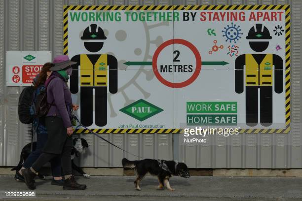 People walk their dogs next to a Work Safety rules board in Dublin city center. On Tuesday, November 17 in Dublin, Ireland.
