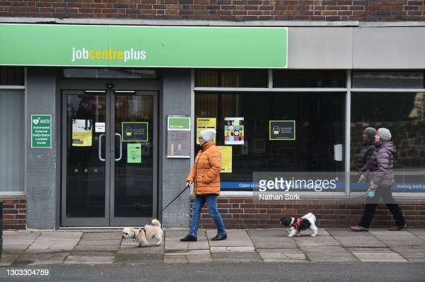 People walk their dogs past a Jobcentre employment office on February 21, 2021 in Tunstall, England.
